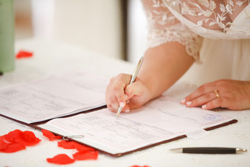 bride signs marriage certificate with a pen