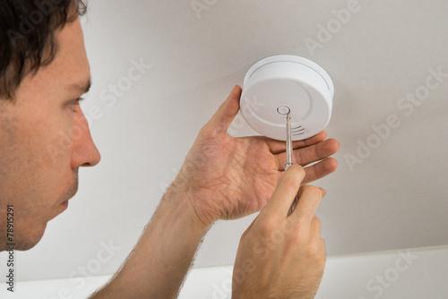 Electrician Repairing Fire Sensor - 78915291