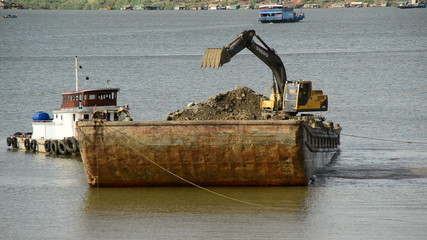 Time Lapse of Excavator on Barge Fills Dirt into Cambodian River - Phnom Penh Cambodia