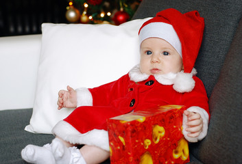 Christmas baby with a Christmas tree background and a present