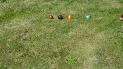 Hand put colorful painted eggs in a row and throw them to crash
