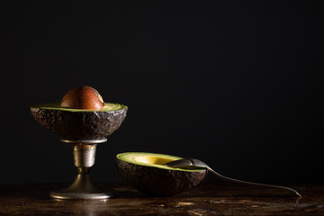 Avocado half in the shell with seed and a spoon. On black