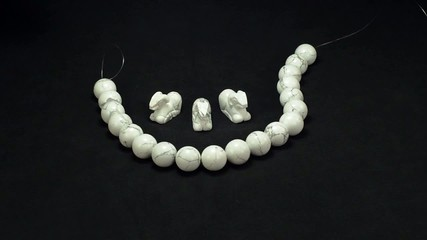 Hands putting white howlite items