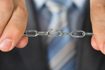 Close-up Of Man Holding Broken Chain