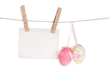 Colorful easter eggs and blank photo frame hanging on rope