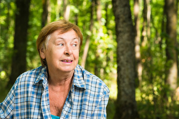 Surprised old woman in the forest
