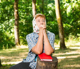 grandmother prays to God in the forest