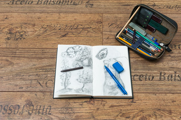 sketchbook with beginner pencil drawings and pencil leather case