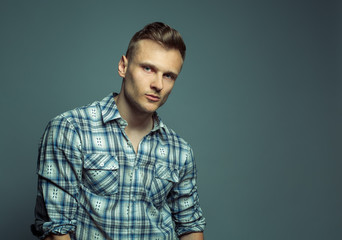 Fashion portrait of young handsome blond man in shirt poses over
