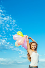 Little pretty blond girl with bright colorfull baloons over blue