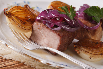Meat with caramelized onions on a plate closeup. horizontal