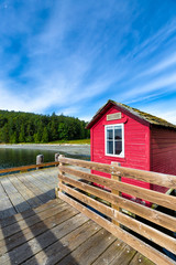 Rustic harbor dock with a wooden hut painted red