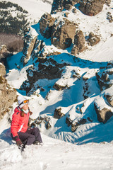 Woman explorer skier in mountains with snowy background