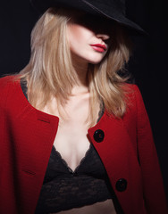 Mysterious fashion portrait of blond woman with red lips in blac