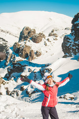 Cheerful woman skier in rocky mountains with snow