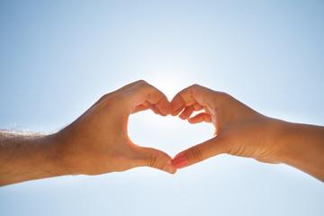 Hand Making Heart Shape Against Sky