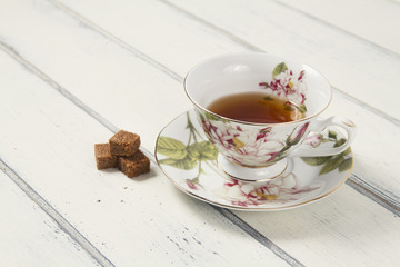 A tea cup with brown cane sugar cubes on a table. Vintage Style.