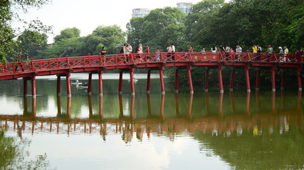 People Walking over The Huc Bridge on Hoan Kiem Lake - Hanoi Vietnam