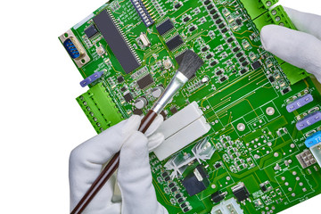 White gloved hands and brush cleaning computer circuit board cpu