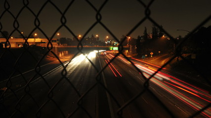 Time Lapse of Traffic through Chain Link Fence