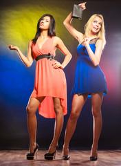 Two dancing women in dresses.