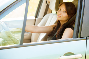 Woman driver hands holding steering wheel of a car
