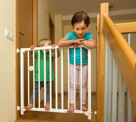 Two  girls approaching safety gate of  stairs