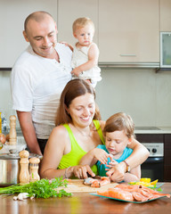 family of four in the kitchen preparing seafood