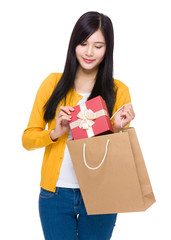 Woman take giftbox from shopping bag