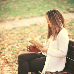 Woman reading a book at bench in autumn park