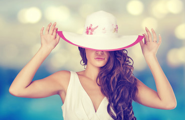 Elegant woman in a white hat on the beach.