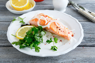 Red fish on a plate with lemon and parsley