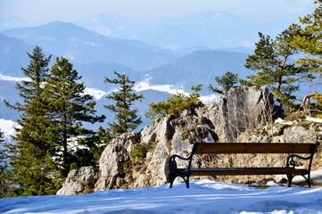Sitzbank vor winterlicher Gebirgslandschaft