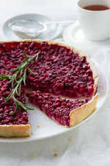 Red bilberry tart with a cup of tea