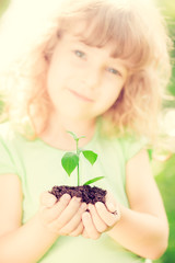 Child holding young green plant in hands. Earth day concept