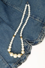 pearl necklace on jean fabric