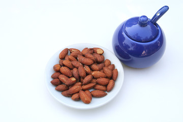 almond with salt pot on white background