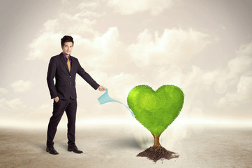 Business man watering heart shaped green tree