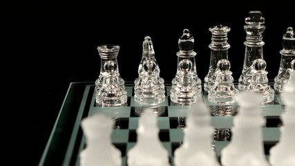 4K. Glass chess board on black background. Crane shot