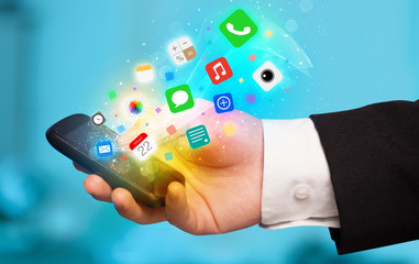 Hand holding smartphone with colorful app icons