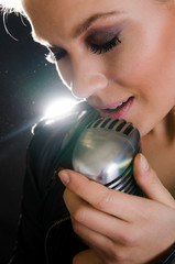 Woman singing into retro microphone