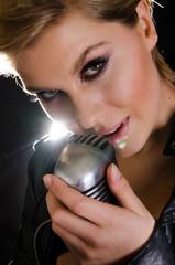 Female rocksinger caressing microphone