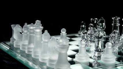 4K. Glass chess on chesboard. Black background.