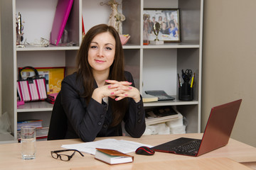 employee in office confident sitting at table with closed arms