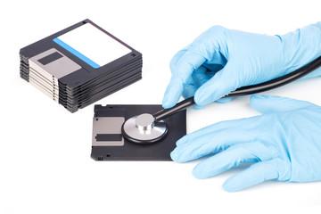 Hand mit einem Stethoskop auf Diskette