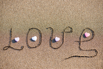 "Word ""love"" on sand background"