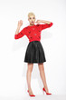 Glamour. Blonde Posing in Red Blouse and Black Skirt
