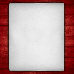 white sheet of paper with on red wooden background