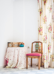 Vintage style interior with table, chair and floral curtain