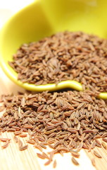 Cumin seeds pouring out of yellow bowl